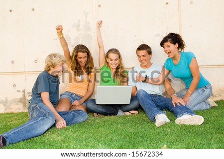 students looking happily at good news on pc - stock photo