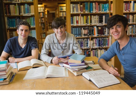 Students looking up from studying and smiling in the library - stock photo