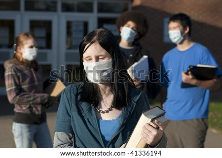 Students of various ethnic backgrounds wearing masks in front of a school. Focus on teen girl in front. - stock photo