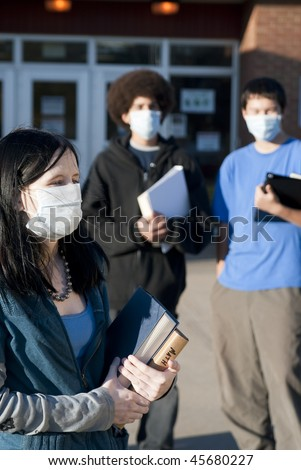 Students of various ethnic backgrounds wearing masks in front of a school. Shallow DOF. Focus on Caucasian girl - stock photo