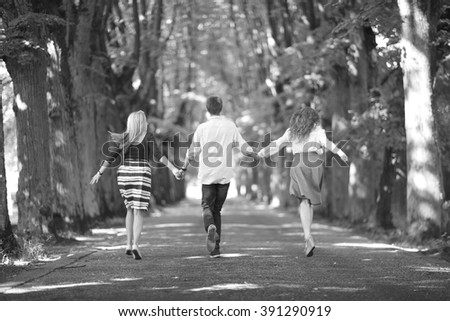 Students on holidays; back view of three young people holding hands together and running through alley  - stock photo