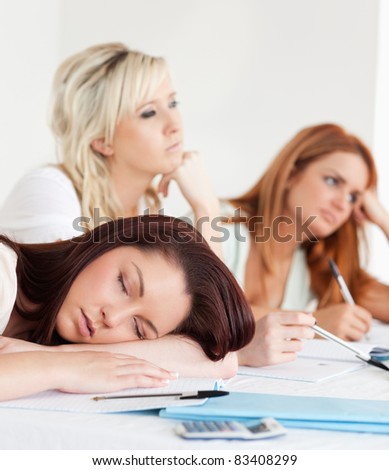 Students one sleeping sitting at a table during class