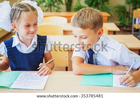 Students or classmates in school classroom sitting together at desk. They are dressed in school uniforms. On table there is a notebook and a pen. The class at background there are plants