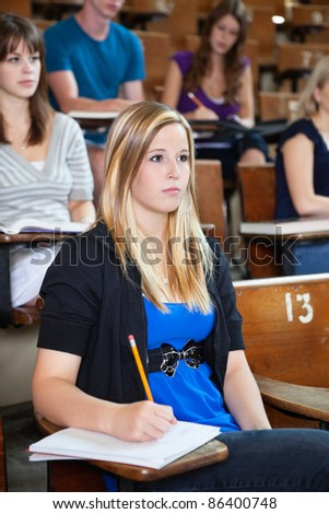 Students paying attention in lecture at seminar hall - stock photo