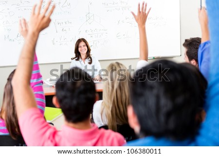 Students raising their hands and asking questions to the teacher - stock photo