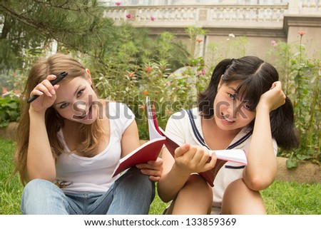 Students reading book in park. Happy caucasian and asian girl studying outdoor in university campus. - stock photo