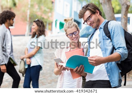 Students reading book while their friends interacting in the background - stock photo