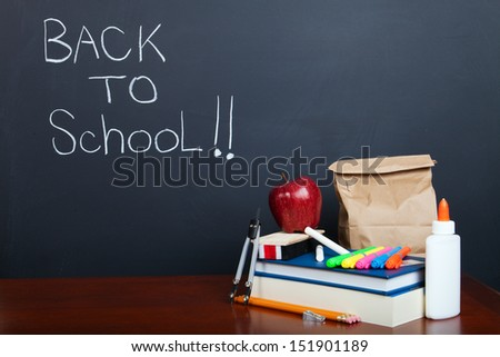 Students school supplies and lunch on desk in front of a chalkboard. - stock photo