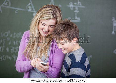 Students sharing a joke in the classroom with cellphone - stock photo