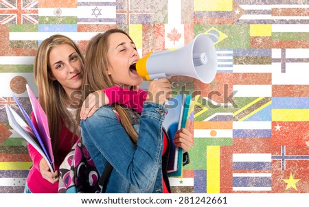 Students shouting by megaphone over flags background - stock photo