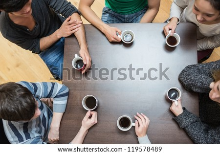 Students sitting around table drinking coffee in college cafe - stock photo