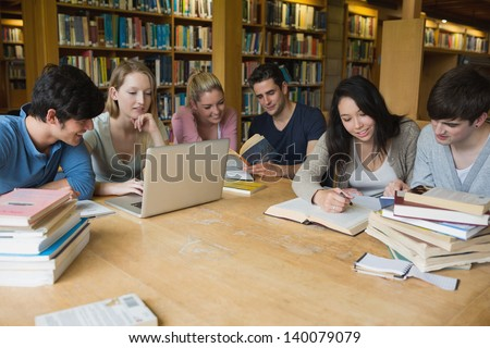 Students sitting at a table in a library while learning and working on a laptop - stock photo