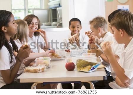 Students sitting at cafeteria table eating lunch - stock photo