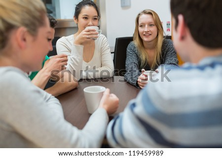 Students sitting at the table drinking coffee talking - stock photo