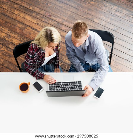 Students sitting at the table using laptop. - stock photo