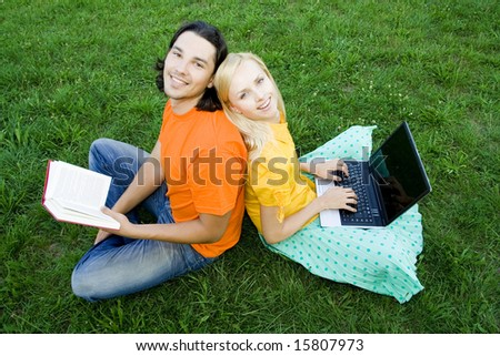Students sitting back to back on grass - stock photo