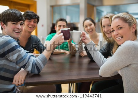 Students sitting clinking cups while smiling in college cafe - stock photo