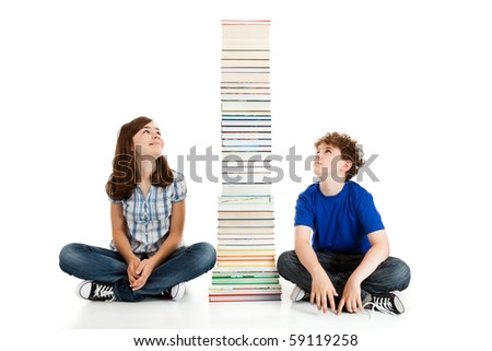 Students sitting close to pile of books on white background - stock photo