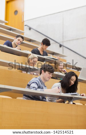 Students sitting in a lecture hall while learning and taking notes - stock photo