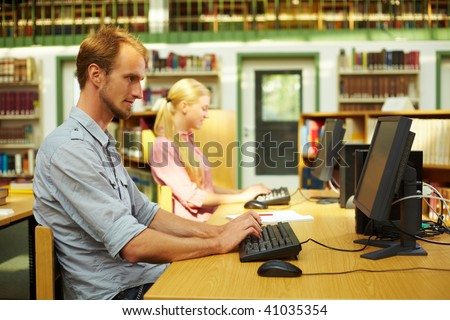 Students sitting in library and using computers - stock photo