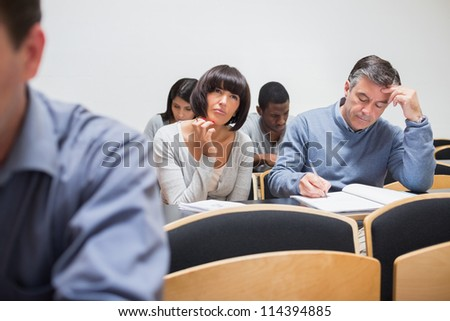 Students sitting in the adult class and thinking while taking notes