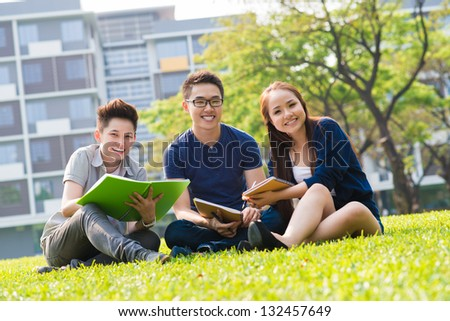 Students sitting on campus lawn and smiling - stock photo