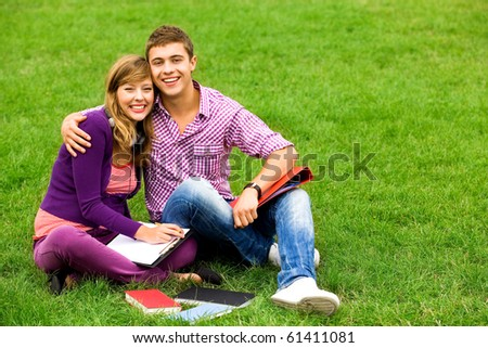Students sitting on grass - stock photo