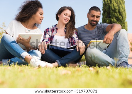Students sitting on the grass at School Campus - stock photo