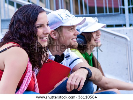 students sitting on the stairs of a schoolyard - stock photo