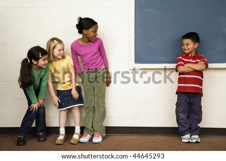 Students standing in classroom. A boy is separate from the girls. Horizontally framed shot. - stock photo
