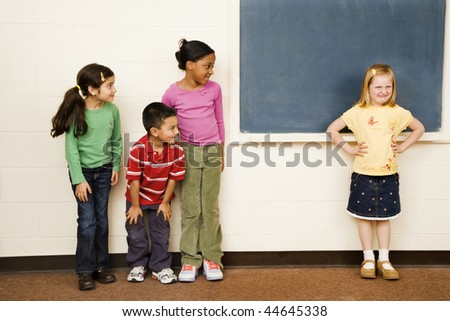 Students standing in classroom. A girl is separate from the group. Horizontally framed shot. - stock photo