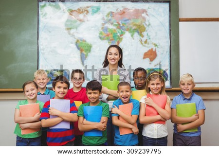 Students standing with the teacher at the elementary school - stock photo