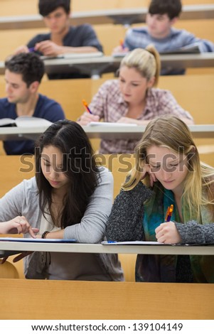 Students studying in a lecture hall with one girl using tablet pc in college - stock photo