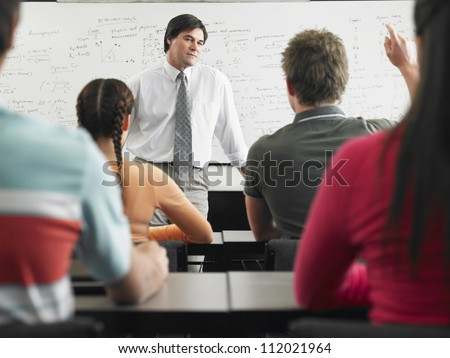 Students studying with professor in classroom