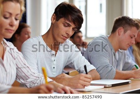 Students taking a test in university class - stock photo