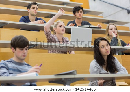 Students taking an active part in a lesson while sitting in a lecture hall - stock photo