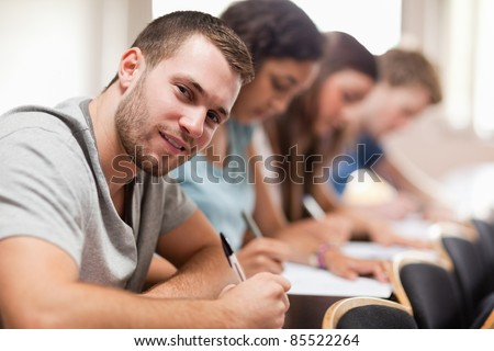 Students taking an exam in an amphitheater - stock photo