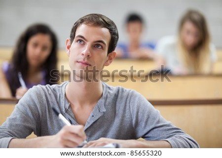 Students taking notes in an amphitheater with the camera focus on the foreground - stock photo