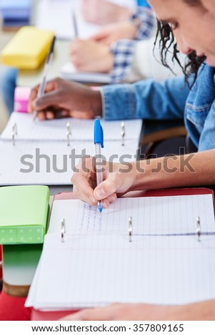 Students taking notes in class with their notebooks - stock photo