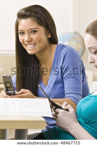 Students text messaging on cell phones - stock photo