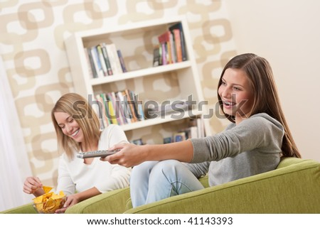 Students - Two smiling female teenager watching television in modern living room