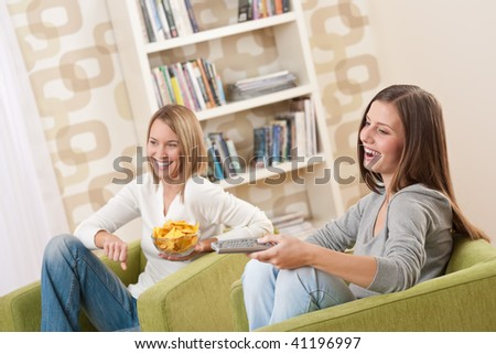 Students - Two smiling female teenager watching television in modern living room - stock photo