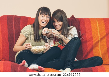 Students - Two smiling female teenager watching television in modern living room, focus on remote control - stock photo