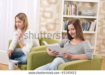 Students - Two teenage girls with laptop and book in modern lounge