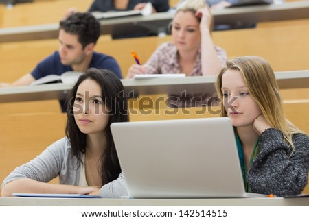Students using the laptop while sitting in a lecture hall and taking notes - stock photo