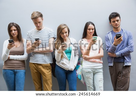Students using their smartphones in a row at the university - stock photo