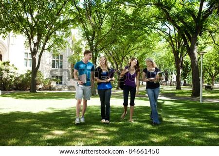 Students walking through campus visiting - stock photo