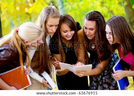 Students with books on nature background - stock photo