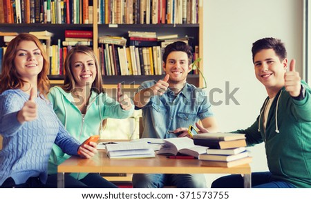 students with books showing thumbs up in library - stock photo