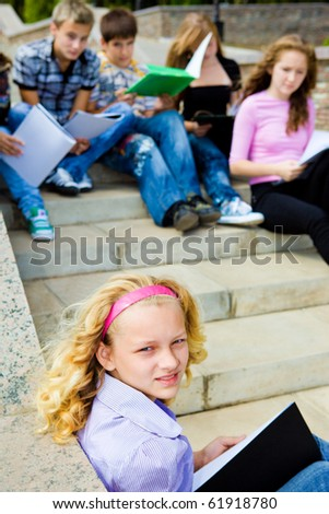 Students with books sitting on a stairway - stock photo